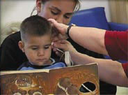 a boy reading with his mother while getting his hearing tested