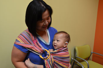 a mother holding her baby close in a cloth sling, both smiling