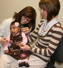 a baby, mother, and audiologist, hearing screening test in progress