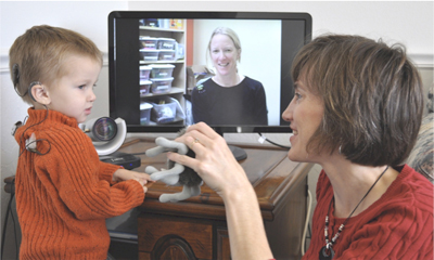 a telehealth session, the child and mom communicating with a health professional with their TV